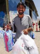 A beneficiary in Iraq carries an UMCOR bag full of the hygiene supplies that will meet the needs of every member in his family. Photo by GlobalMedic, courtesy of UMCOR.