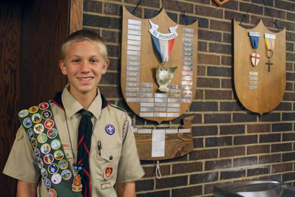 Eagle Scout Landon Kohtz, 15, poses in front of scouting plaques. Photo courtesy of Landon Kohtz.