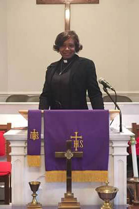 The Rev. Jackie Ford poses in the pulpit of her church.