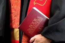 The 2012 edition of The Book of Resolutions of The United Methodist Church is held by an ordained clergy. Photo illustration by Kathleen Barry, United Methodist Communications