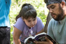 A child studies a Bible with a camp counselor.