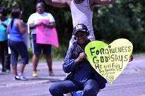 A demonstrator in Ferguson, Missouri holds a poster about forgiveness after the shooting of Michael Brown led to days of racial unrest in 2014. Image by Loavesofbread, shared via Wikimedia Commons.