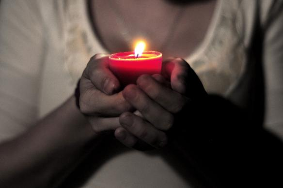 Woman holds candle. Photo by Courtney Carmody, courtesy of Flickr.