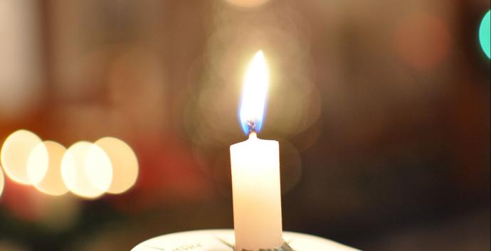 A candle burns during a service. Photograph by Angelia Sims of Angelia's Photography.