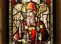 A stained-glass window in the United States depicts St. Patrick with his staff and holding a church. Wikipedia Creative Commons.