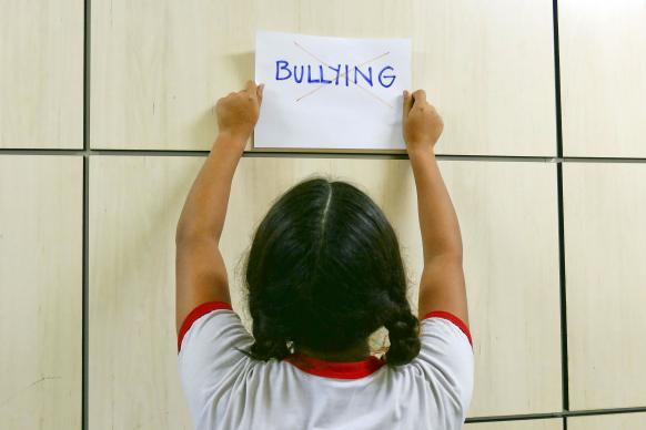 Child holds anti-bullying sign. Photo illustration courtesy of Wikimedia Commons/Senado.