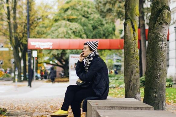 A woman sits outdoors on a bench while talking on a phone. Photo by Gabriel Santiago, courtesy of StockSnap.io.