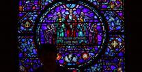 A woman stands silhouetted against a stained-glass window outside the Upper Room chapel. Photo by Kathleen Barry, United Methodist Communications.