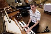 Chase Crispin, a senior at Nebraska Wesleyan University, practices the organ at First United Methodist Church. His interest inspired the church's music director, Brent Shaw, to start a scholarship at Wesleyan. Photo by Emily Case, Journal Star