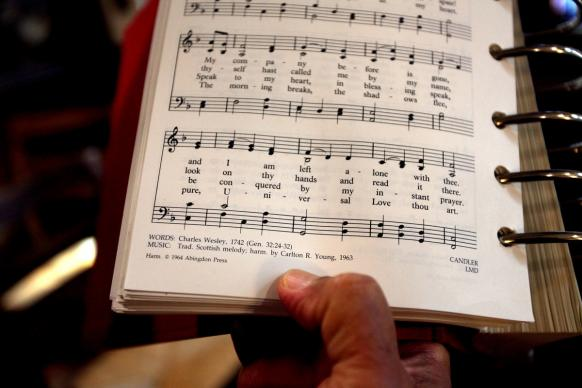 The Rev. Romero del Rosario holds a songbook featuring the lyrics written by Charles Wesley in 1742, Come, O Thou Traveler Unknown. Photo by Kathleen Barry, United Methodist Communications.