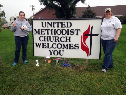 The Rev. Andrea Beyer (left) and the Rev. Cathryn Love stand near a church sign in Beaver Crossing, Nebraska. Image courtesy of Great Plains Conference/creative commons.