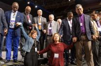 Florida delegates Rachael Sumner (front left) and the Rev. Jacqueline Leveron (front right) of the Florida Conference join in prayer with bishops and other delegates at the front of the stage before a key vote on church policies about homosexuality during the 2019 United Methodist General Conference in St. Louis. Photo by Mike DuBose, UMNS