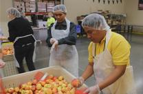 Joselito Javien Ortiz of the Philippines bags produce at the Oregon Food Bank as part of a volunteer effort during General Conference 2016.Video image by United Methodist Communications.