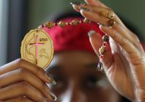 Woman displays a set of prayer beads created for General Conference 2016. Photo by Kathleen Barry, United Methodist Communications.