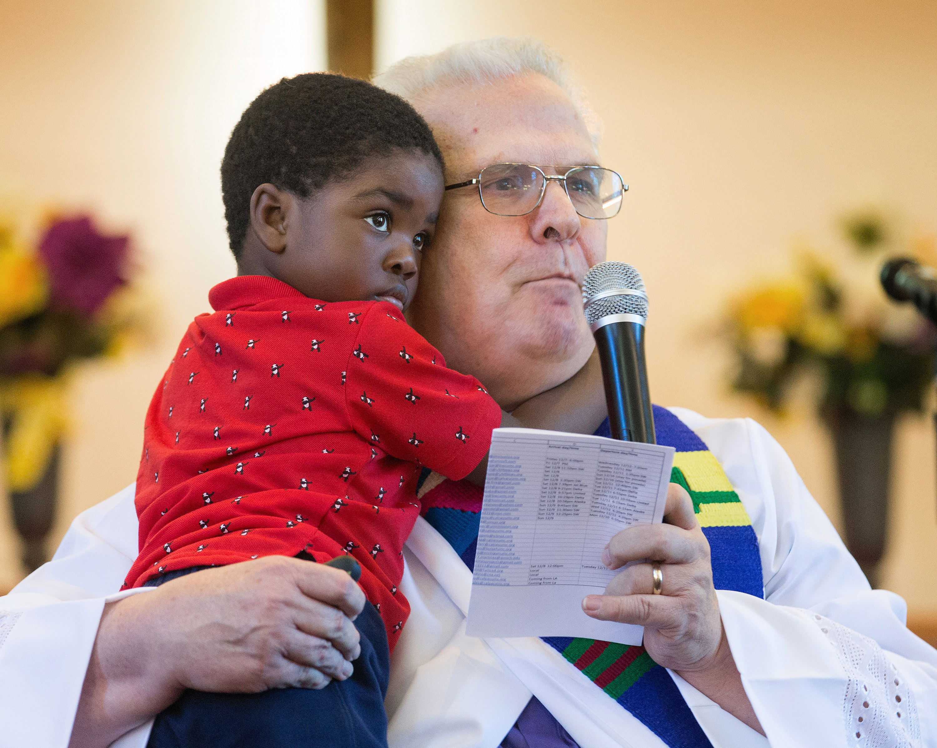 TThe Rev. Bill Jenkins gives the sermon during worship at Exodus United Methodist Church in San Diego while holding his foster son Harry, who is from Haiti. The church is the only immigrant-welcoming center in Southern California. Photo by Mike DuBose UM News.