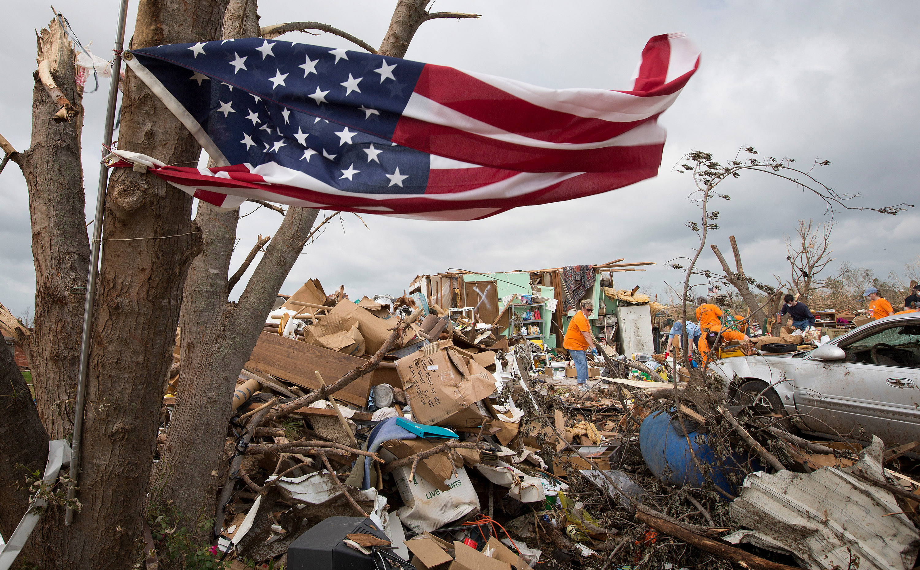 A salvaged U.S. flag flaps in the breeze of a building storm while a volunteer team cleans up tornado damage at a home in Moore, Okla. The team was working out of First United Methodist Church in Moore. Photo by Mike DuBose, UM News.