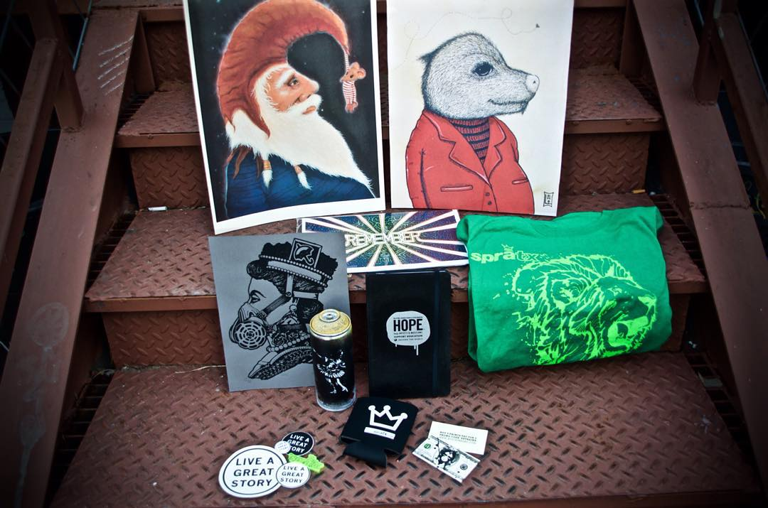 PRIZE PACK GIVEAWAY  INCLUDES: Spratx koozie, HOPE notebook, LIVE A GREAT STORY stickers and button, one Lucas Aoki print, limited run Spratx key chain, MOUF T-shirt, one coupon for prints from Black Ink Arts, Wanderweird REMEMBER Booklet, and Dave...