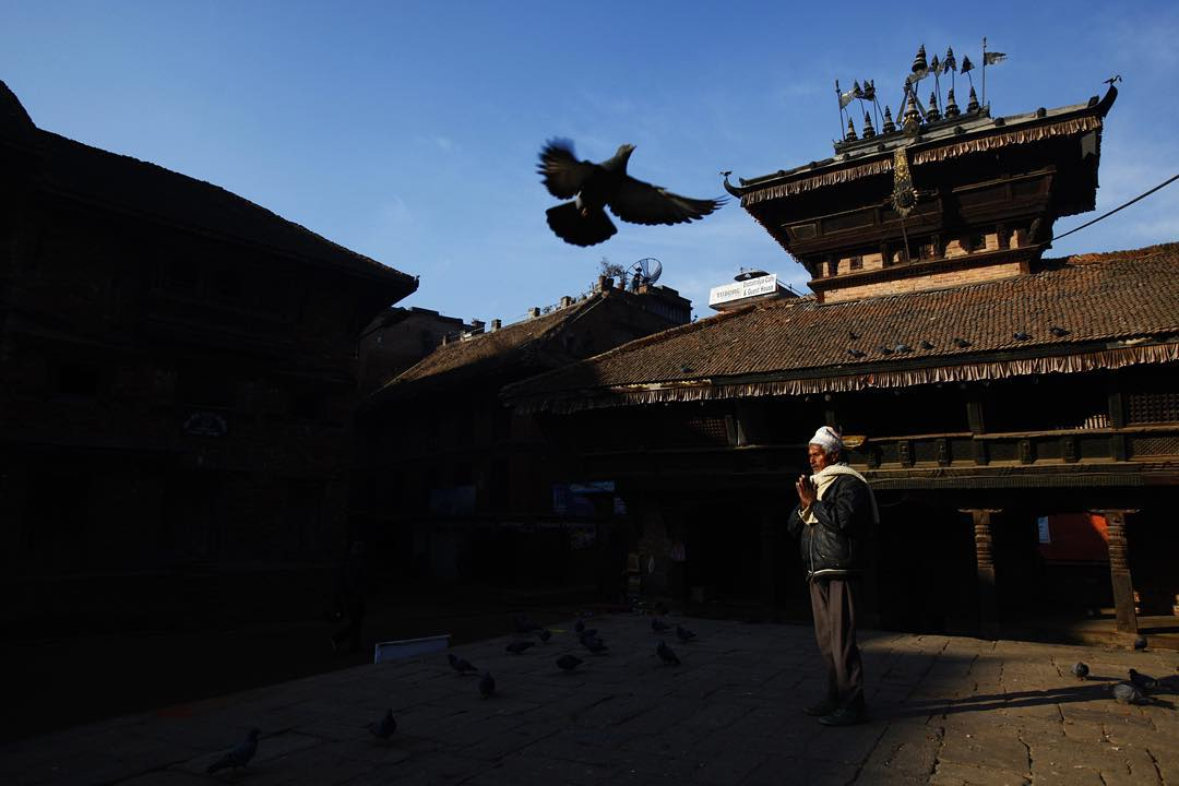 An elderly man offers a prayer to a temple in the ancient city of Bhaktapur; also known as the city of devotees.
