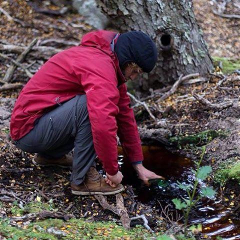 Cargando la botella de agua en el chorrillo donde acampamos.