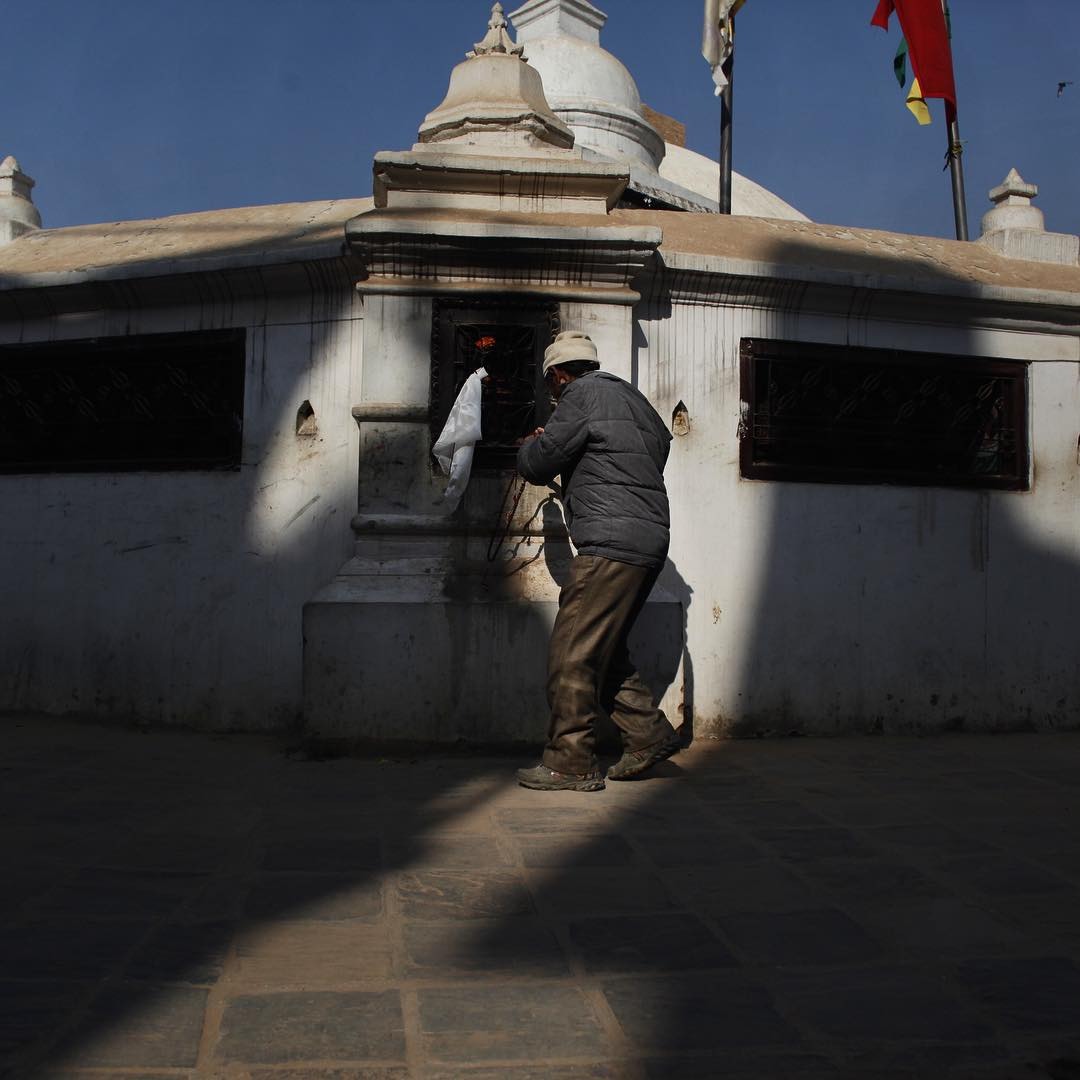 "A man receives blessings during circumambulation at Boudha Stupa. Doing ""korwa"" or circling holy objects clockwise destroys negative karma and creates good fortune according to Tibetan Buddhists. This stupa dating back to the 6th century is circled by..."