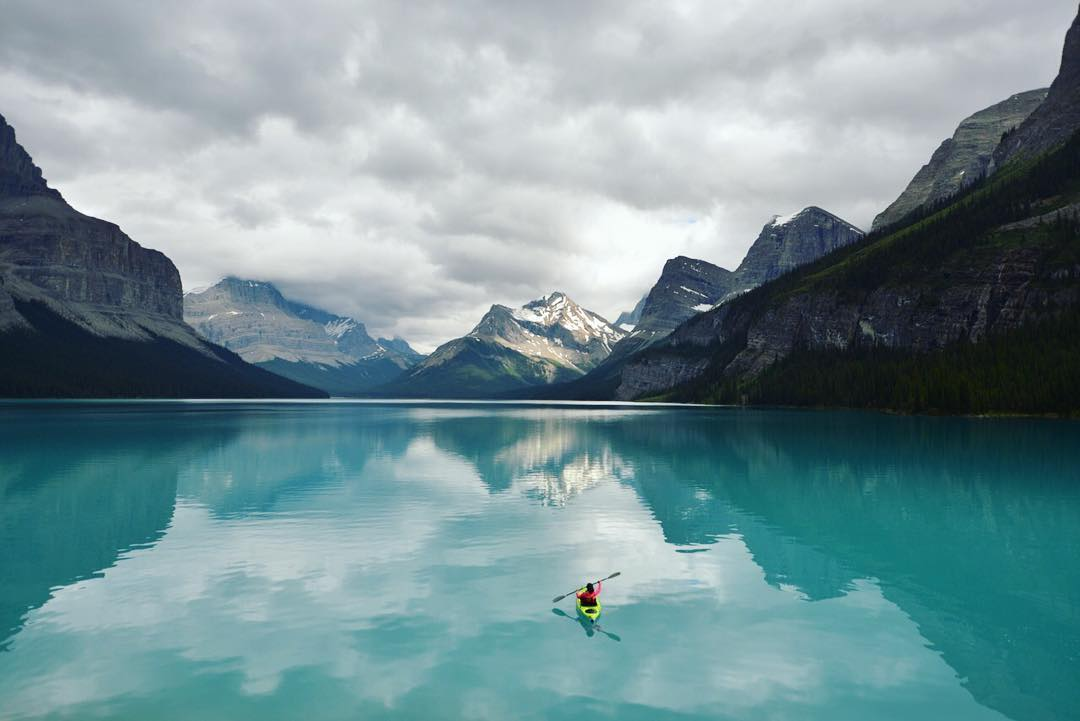 The morning brought us moody cloud covered skies . It made the colours of Maligne Lake pop vividly. With a crown of mountains around us, it truly felt like the land before time.  Paddler: @expedsbella