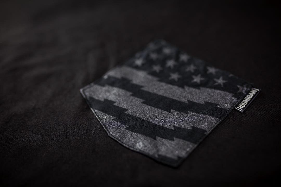Detail shot of our Gymkhana_EIGHT pocket tee. The tonal, black on black, Stars and Stripes with an ultra reflective tag logo. Available on #hooniganDOTcom