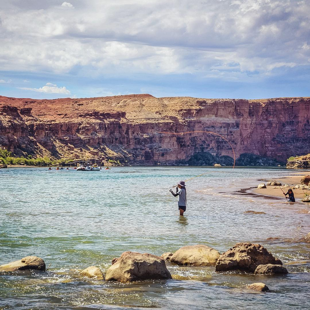 A local tries his luck fly casting while his son plays on the bank and a raft full of adventurers sets out from Lee's Ferry and into the Grand Canyon.