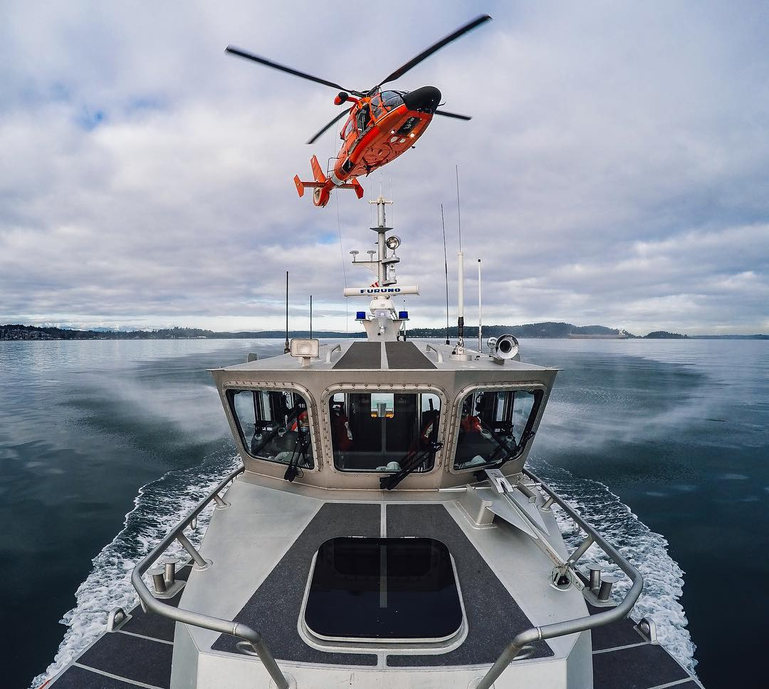 "Photo of the Day! A @uscg MH-65 Dolphin practices ""hoisting and personnel recover"" during a search + rescue training evolution in the Puget Sound. Keep up the good work and thank you #USCG for keeping our waterways safe! #"