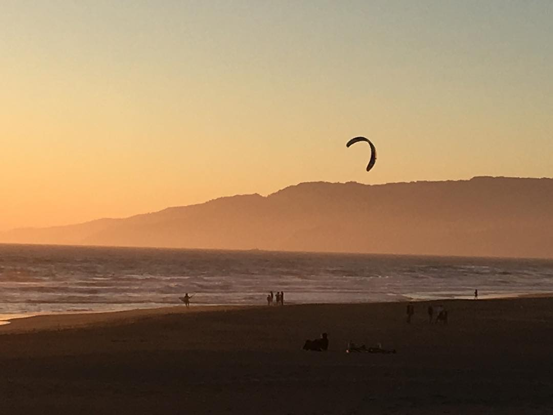 Summer sunsets in San Francisco *please remember to  bring your wetsuit . #mafiateam #fromsailstobags . This picture was taken by @pedrobalaphotography while running on the beach - Marcos Mafia & his kite going upwind.