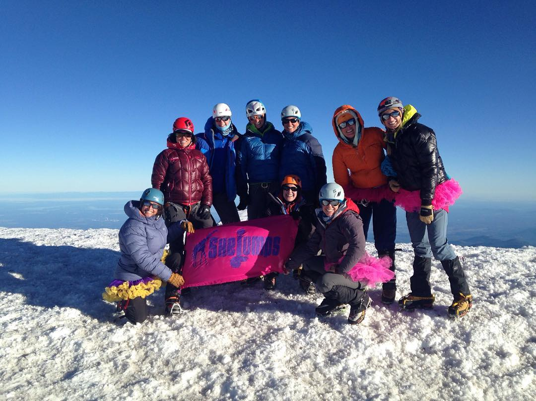 Rainier Climb Series 5/5: On top of Rainier the group posed for a quick summit photo with tutus and our flag. There were a lot of powerful women on the mountain that weekend, and even more behind the scenes, far away from Rainier. What these women...