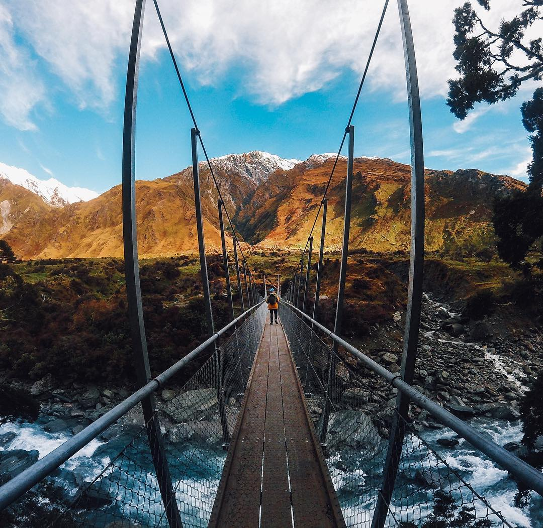 Photo of the Day! To access the #RobRoyGlacierTrack at the base of #MountAspiring, you've got to handle this suspension bridge. @leahalwayslost proves the journey itself can be worth it! Those mountains are beautiful. #GoPro #GoProANZ #GoProTravel #