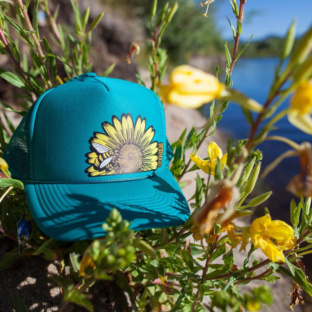 Just restocked these Bee Flower Trucker Hats in Jade. Grab one today www.risegraphics.com - free shipping #risedesigns #risedesignstahoe #sunflower #bee #truckerhat #laketahoe #outdoors