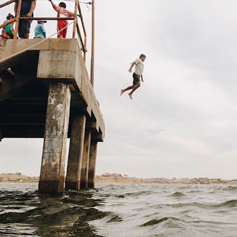 """Swim class was so incredible. 3 kids who had never swam before, were brave enough to get in and get wet. Felix, pictured, takes the plunge from the fishing pier!"" ✨ Recollection of @ryanstruck's volunteer visit to Lobitos, Peru."