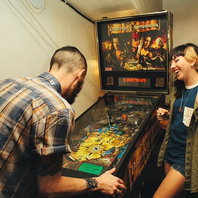 "Ambig advocate/artist/naive thieve frontman @cameronthorne playin some pinball in the ""GARCIA"" button up with all-around-rad chick @bent_and_broken  #ambigclothing #pinballwizard"