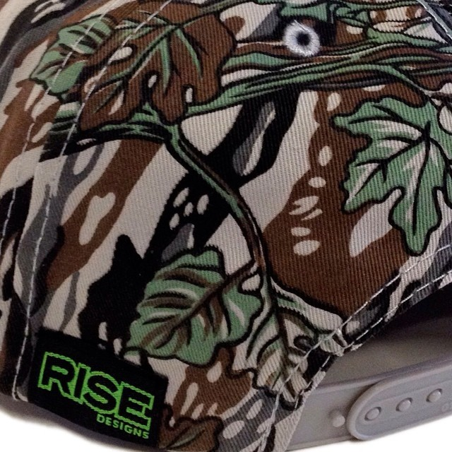 Close up of our Sunrise Patch Snapback Hat. Tree Camo print w/ custom RISE label. #risedesigns #snapback