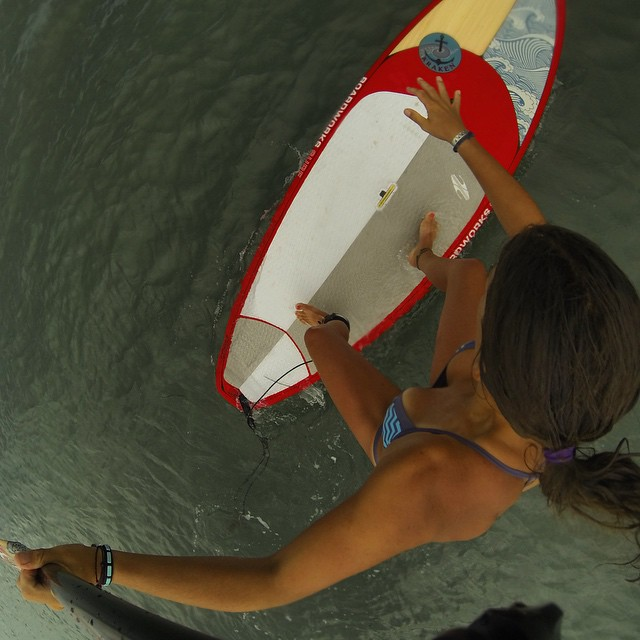 Birds eye view of a river mermaid learning how to sup surf. Not so graceful..