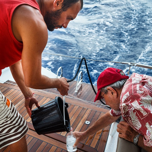 """[Rinsing] the bucket 3 times, the bottle 3 times at 10 knots is a lot of work and action!"" said Phillippe Tarbouriech, who took this photo of Riccardo Miglia and Jérôme Winter collecting #ASCMicroplastics samples during the ARC Atlantic Rally for..."