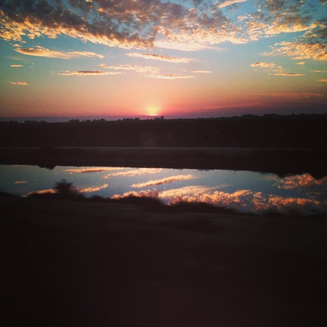 On a Train running next to an irrigation canal that is reflecting the setting sun. #california #beauty #sunset