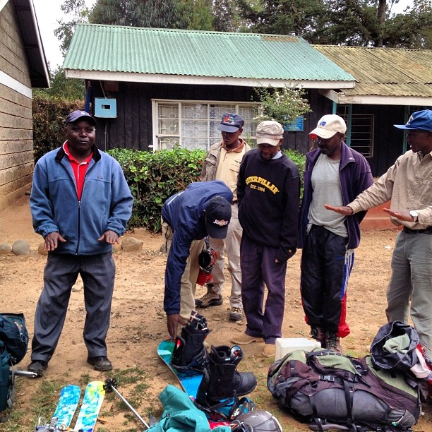 Simon explains #skiing and #snowboarding to a group of porters. First time seeing #skis and #boards in real life and not sure what to make of the two women who rode them down the Lewis Glacier. #summitforoursisters #kenya #africa #tbt @zawadisha