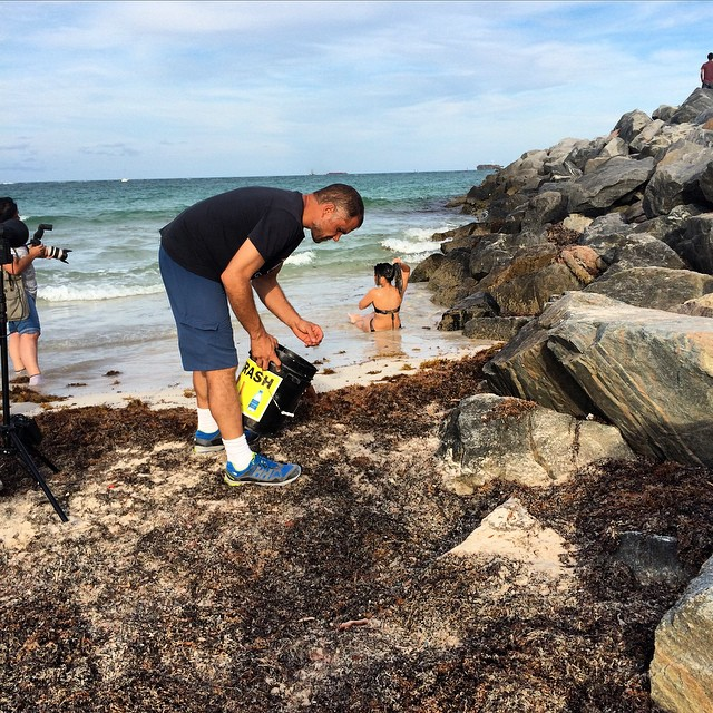 South Beach, Miami. Great turnout at the first cleanup of the @5gyres Sea Change expedition. Seen here, @marcus.eriksen briefly interrupting a photo shoot to clear the runway. @surfrider @debrisfreeoceans