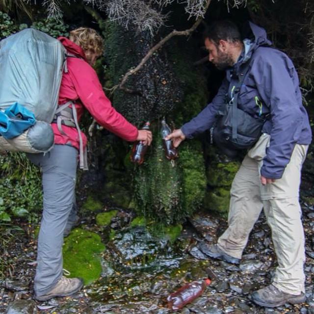 Julian y Sergio recargando las botellas de agua al pie de un acantilado.  El color del agua oscura se debe a la turba que le da un poco más de acidez y color rojizo.