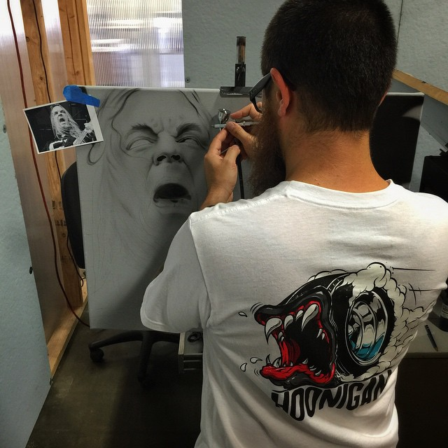 This is how our art director @jchase7452 (wearing the new Creature of the Hoon Tee, which he also drew) spends his lunch break... First person to correctly name the subject he is airbrushing will win something rad. [Find the Tee on #hoonigandotcom]
