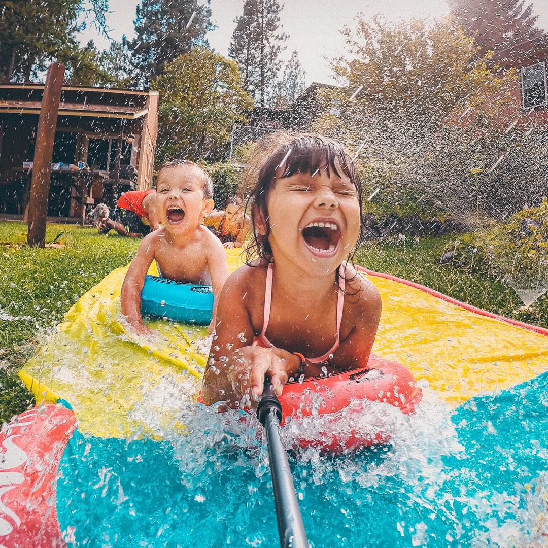 Photo of the Day! Lily and Eli beat the summer heat in the best possible way...a slip-n-slide! Photo via @joekonekphotography. Submit your best photos by clicking the link in our profile! #GoPro #Family #Summer