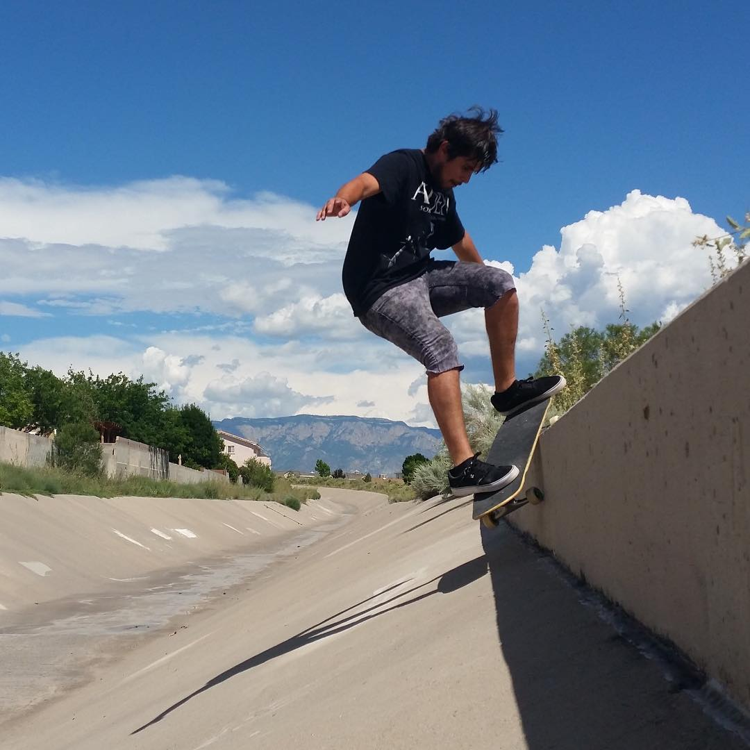 Flow rider @deadbear13 dips a FS Smith on his #parisstreetrucks on this beautiful bank-to-ledge in the ditch paradise of ABQ, NM.
