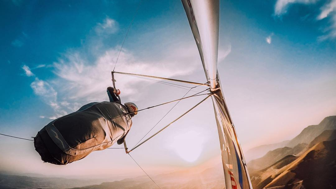 Photo of the Day!  @matjazklemencic soaring high above the Italian #sunset, enjoying an evening flight. Share your best moments with us by clicking the link in our profile. #GoPro #hanggliding