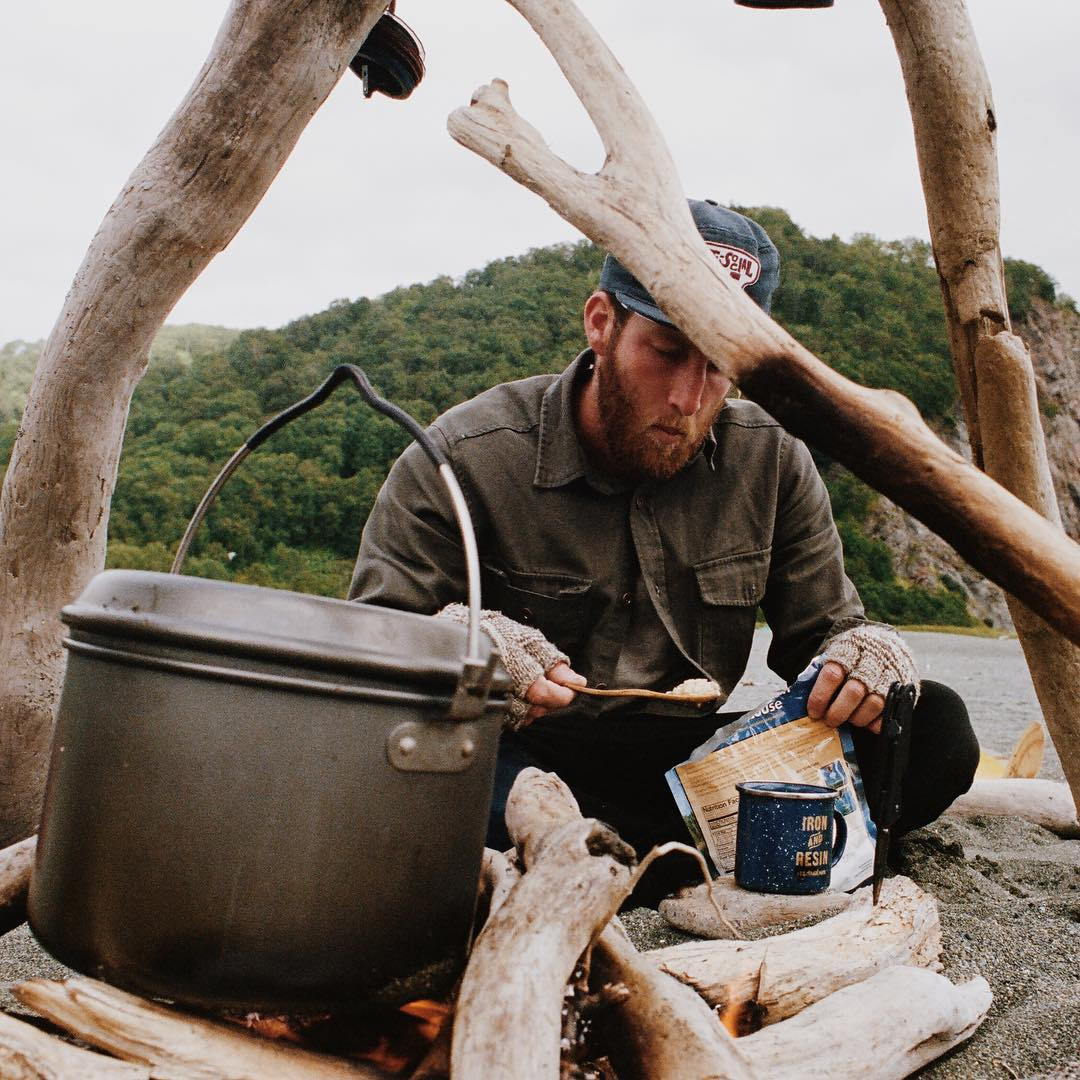 The upside of forgetting a camp stove - it's more fun cooking this way. We kept a driftwood fueled fire going 24/7 to keep the thick cloud of mosquitoes at bay and to make post-surf tea on. This is @dylangordon after a few days straight of dehydrated...