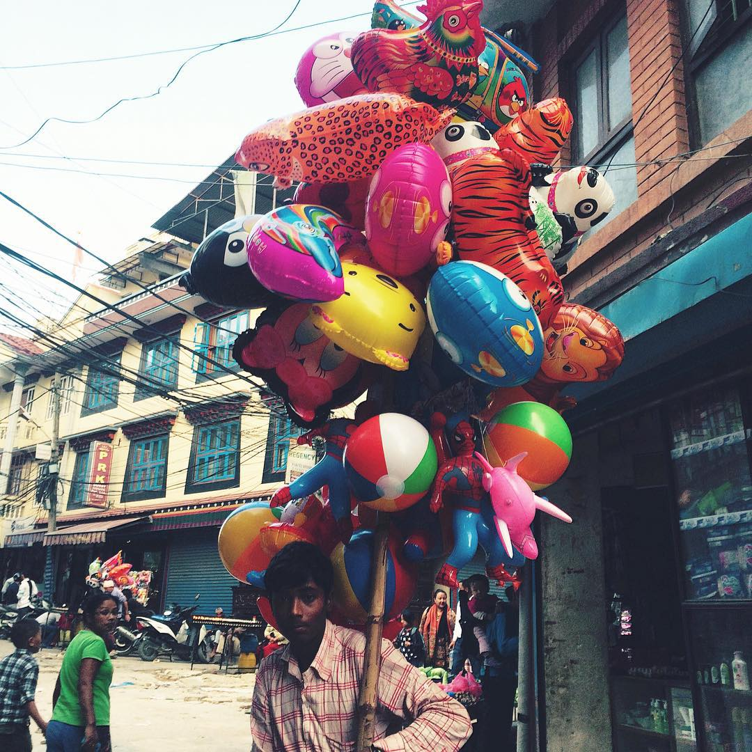 A teenage boy sells colorful balloons in Kathmandu, as all across the city and country people begin to celebrate Dashain, a 15 day long festive Hindu holiday. #connectglobally #nepal #estwst