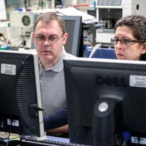 man and woman sitting at computers