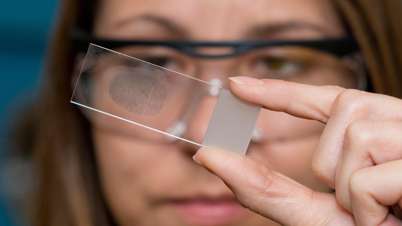 Woman inspects finger prints on slide