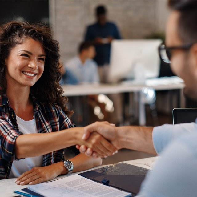 Woman and man shaking hands across desk